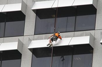 Trabajador suspendido en una fachada realizando trabajos verticales.