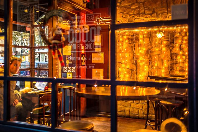 Fachada exterior de cafetería decorada con tonos vivos y grandes cristaleras.